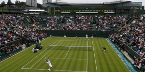 Marcos Baghdatis of Cyprus, foreground, serves to Marin Cilic of Croatia during their Men's first round singles match at the All England Lawn Tennis Championships in Wimbledon, London, Monday, June 24, 2013. (AP Photo/Sang Tan)